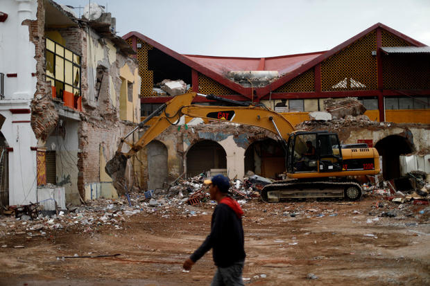 Resident walks near debris and destroyed houses after an earthquake in Juchitan