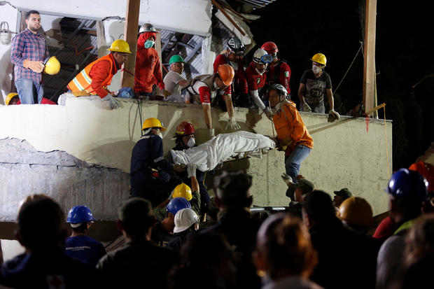 Rescue workers remove a dead body after searching through rubble in Mexico City