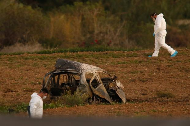 Forensic experts walk in a field after a powerful bomb blew up a car killing investigative journalist Daphne Caruana Galizia in Bidnija