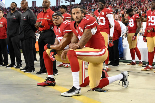 Colin Kaepernick, center, and Eric Reid of the San Francisco 49ers kneel in protest during the national anthem prior to playing the Los Angeles Rams in their NFL game at Levi's Stadium on Sept. 12, 2016, in Santa Clara, California.