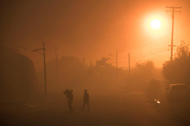A TV crew walks through smoke as they work covering a  wind driven wildfire in Ventura, California