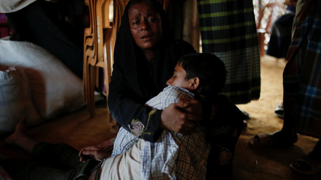 Shajeda Khan cries as she holds her unconscious son Salamat, 14, whose family says he was attacked by relatives of the girl he was arranged to marry but refused, at the Mayner Ghona refugee camp near Cox's Baza