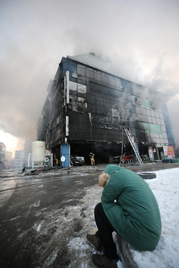 A man who is believed to be a relative of a victim reacts as smoke rises from a burning building in Jecheon