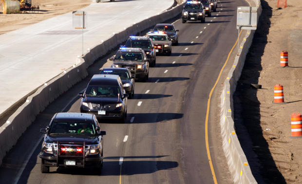A procession of police vehicles escorts the hearse carrying the body of a deputy killed in a domestic disturbance where multiple deputies and civilians were shot in Highlands Ranch