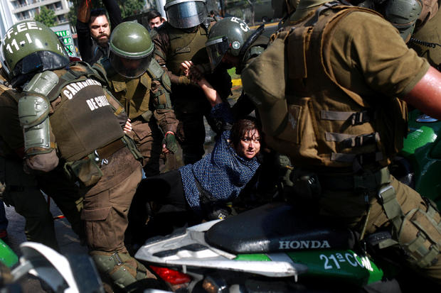A woman is detained during a protest against Papal visit in Santiago