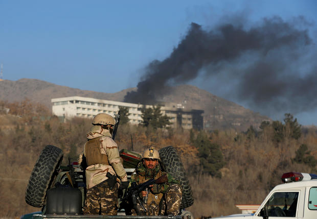 Afghan security forces keep watch as smoke rises from the Intercontinental Hotel in Kabul,ÊAfghanistan