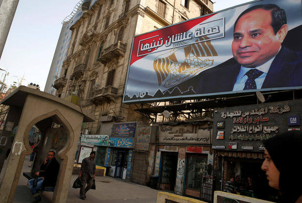 "People walk by a poster of Egypt's President Abdel Fattah al-Sisi from the campaign titled ""Alashan Tabneeha"" (So You Can Build It), for the upcoming presidential election in Cairo"