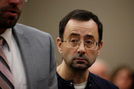 Larry Nassar, a former team USA Gymnastics doctor who pleaded guilty in November 2017 to sexual assault charges, stands with his legal team during his sentencing hearing in Lansing