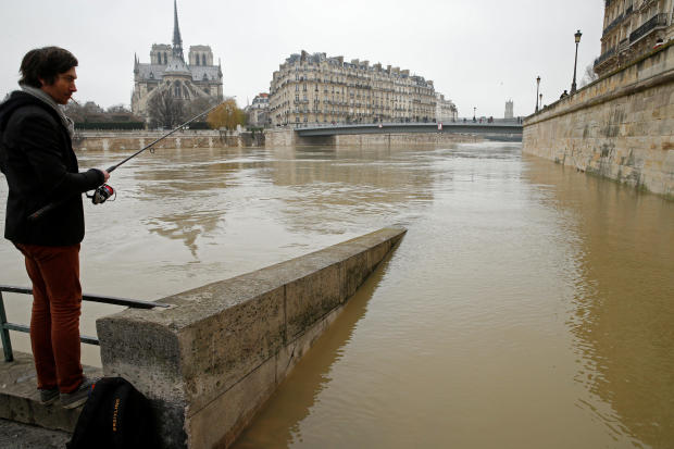A man fishes on the flooded banks of the River Seine in Paris
