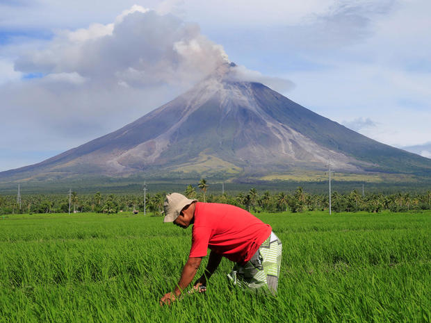A farmer works on a rice farm while Mount Mayon volcano spews ash during a new eruption in Daraga