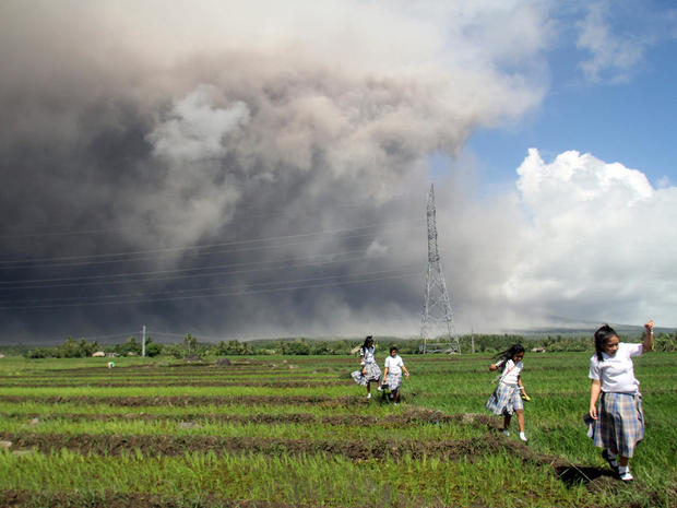 Students passes through the rice paddy as they run away from cascading volcanic materials from the slopes of Mayon Volcano in Guinobatan, Albay province, south of Metro Manila