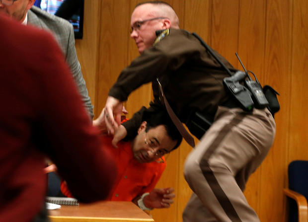 An Eaton County sheriff's deputy protects Larry Nassar, wearing orange, a former USA Gymnastics team doctor who pleaded guilty in November 2017 to sexual assault charges, as he is attacked by Randall Margraves, not pictured, during victim statements in hi
