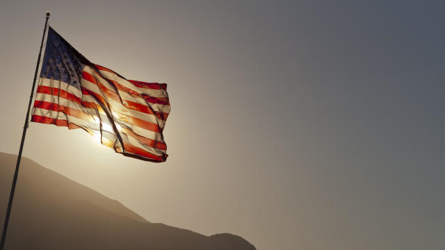 Back-lit American flag flying on pole with copy space.