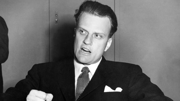 Billy Graham, the American evangelist, pounds his knee as he is interviewed aboard the SS United States on Feb. 26, 1954, upon his arrival in Southampton, England, from New York.