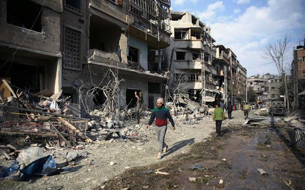 People walk through air raid damage in the besieged town of Douma, Eastern Ghouta, Damascus