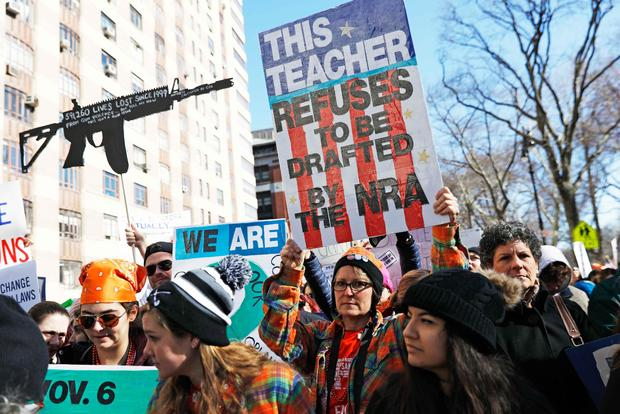 """Protesters raise signs during a """"March For Our Lives"""" demonstration demanding gun control in New York City"""