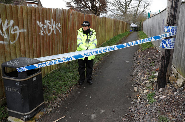 A police officer stands behind cordon tape in an alleyway which has been blocked off near the home of former Russian intelligence officer Sergei Skripal in Salisbury