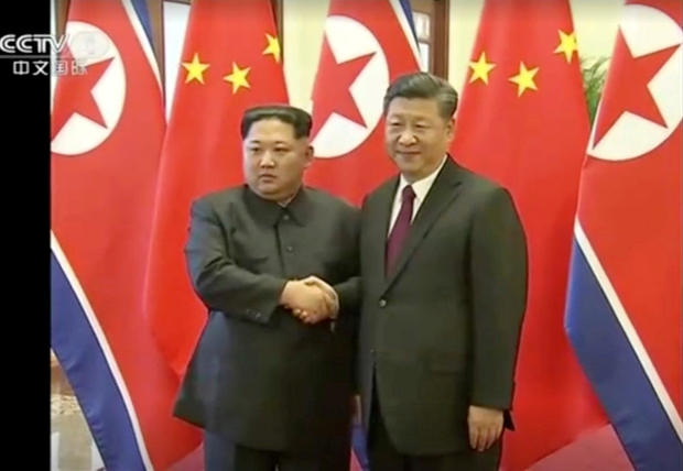 Still image of North Korean leader Kim Jong Un shaking hands with Chinese President Xi Jinping