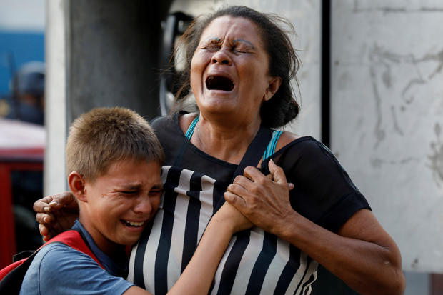 Relatives of inmates held at the General Command of the Carabobo Police react as they wait outside the prison where a fire occurred in the cells area in Valencia