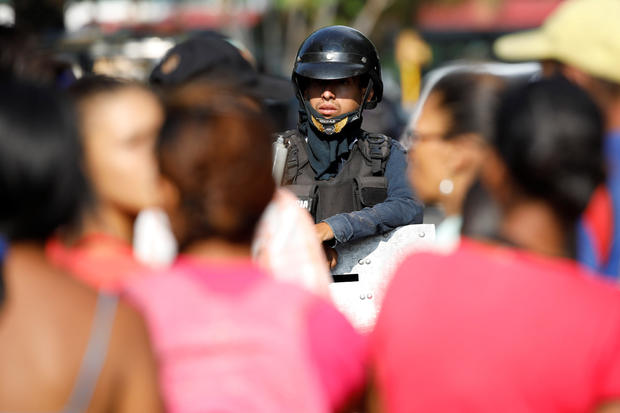 A police officer stands guard outside the General Command of the Carabobo Police prison in Valencia