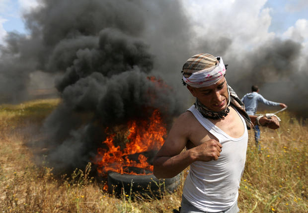 Palestinian runs during clashes with Israeli troops, during a tent city protest along the Israel border with Gaza, demanding the right to return to their homeland, the southern Gaza Strip