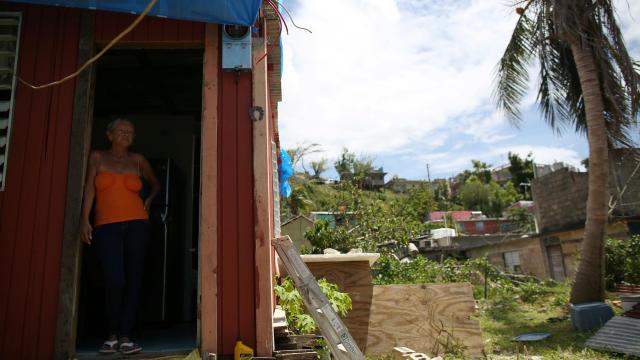 Bexaida Torres stands in the door of what is left of her home after Hurricane Maria hit the island in September, in a neighborhood in Canovanas, Puerto Rico, April 10, 2018.