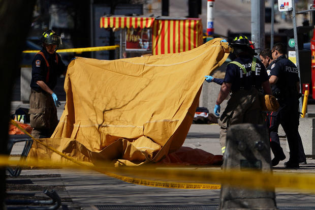 Emergency officials cover a body with a tarp at the scene of an incident where a van struck multiple people in Toronto