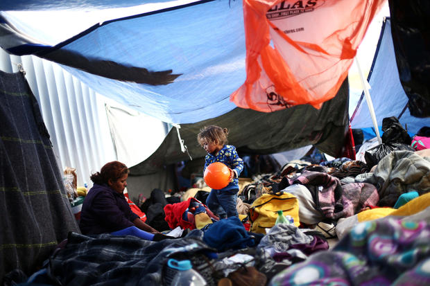 A child traveling with a caravan of migrants from Central America holds a ball at a camp near the San Ysidro checkpoint, after U.S. border authorities allowed the first small group of women and children entry from Mexico overnight, in Tijuana
