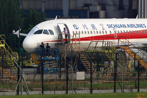 Workers inspect a Sichuan Airlines aircraft that made an emergency landing after a windshield in the cockpit broke off at an airport in Chengdu, China, May 14, 2018.