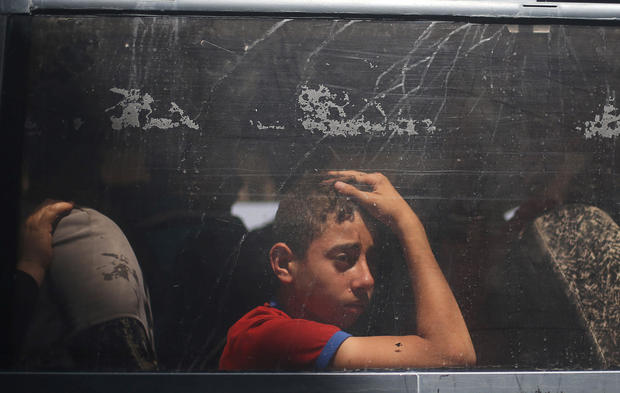 Palestinian boy looks out a bus window as he waits to travel into Egypt through the Rafah border crossing, in the southern Gaza Strip