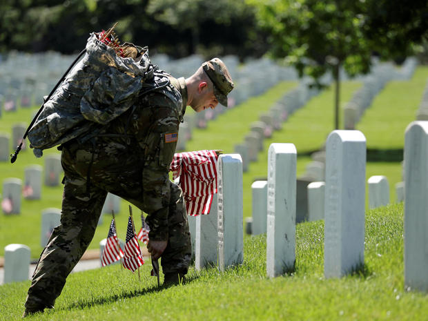 U.S. Army soldiers of the 3rd United States Infantry Regiment arrive to place U.S. flags on graves at Arlington National Cemetery