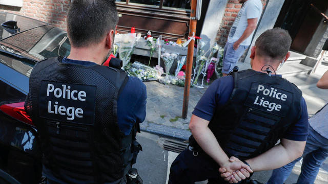 Belgian police officers pay tribute to the victims of a shooting outside of the cafe where the shooting took place in Liege