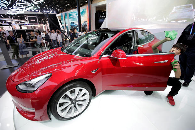 FILE PHOTO: A man cleans a Tesla Model 3 car during a media preview at the Auto China 2018 motor show in Beijing