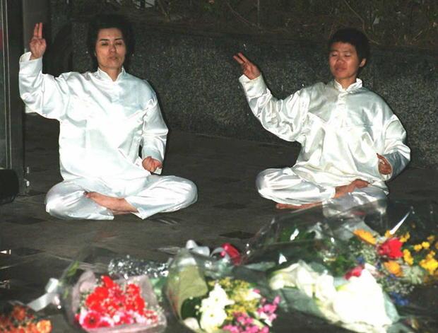 Members of the Aum Shinrikyo (Supreme Truth) sit o