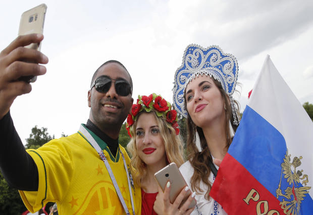 A Brazil fan takes a selfie with Russian supporters in a fan zone near the main building of the Moscow State University in Moscow on June 14, 2018.