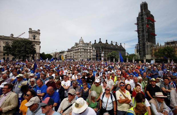 EU supporters, calling on the government to give Britons a vote on the final Brexit deal, listen to a speaker in Parliament Square, after participating in the 'People's Vote' march in central London