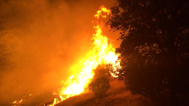 In this photo provided by the California Department of Forestry and Fire Protection, the Pawnee Fire wildfire burns northeast of Clearlake Oaks, California, early on June 24, 2018.