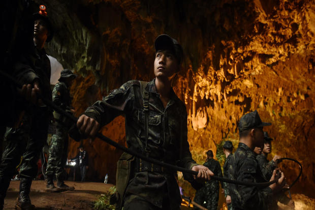 Thai soldiers relay electric cable deep into the Tham Luang cave at the Khun Nam Nang Non Forest Park in Chiang Rai, Thailand, on June 26, 2018, during a rescue operation for a missing children's soccer team and their coach.