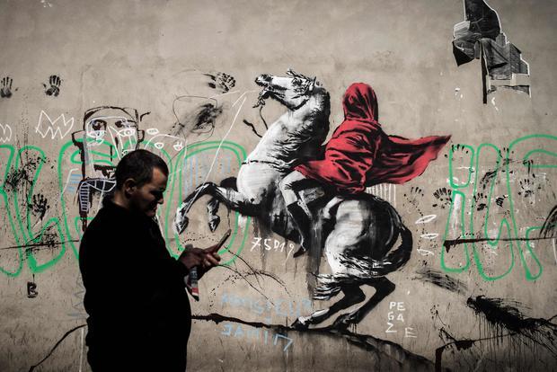 Street artist Banksy paints Paris with murals of migrants