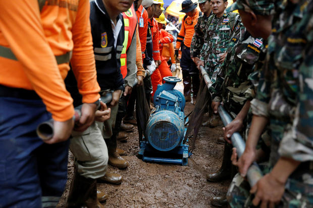Soldiers and rescue workers carry a water pump to the Tham Luang cave complex during a search for members of an under-16 soccer team and their coach, in the northern province of Chiang Rai