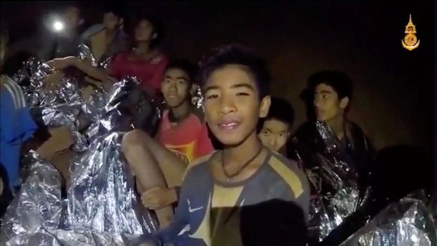 Boys from the under-16 soccer team trapped inside Tham Luang cave covered in hypothermia blankets react to the camera in Chiang Rai, Thailand