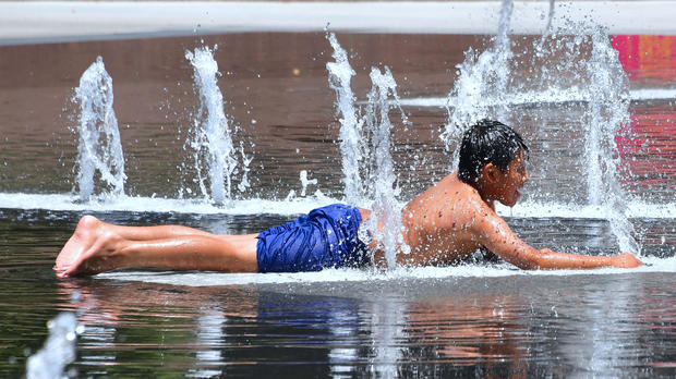 A boy cools off in the water play area at Grand Park in Los Angeles, California, on July 5, 2018, ahead of a heat wave in the Los Angeles area.