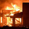 A house burns as firefighters battle flames at a home at the site of a wildfire in Goleta