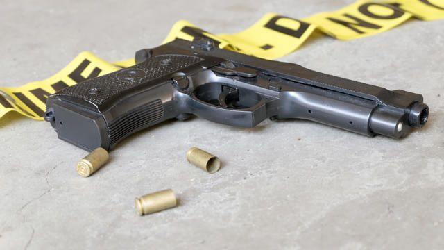 Crime scene concept with gun and three casings - handgun, police tape, generic