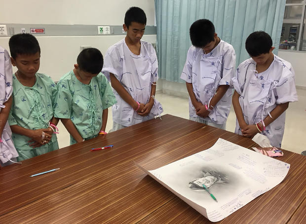 """Members of """"Wild Boars"""" soccer team and their coach rescued from a flooded cave bow their heads after writing messages on a drawing picture of Samarn Kunan at the Chiang Rai Prachanukroh Hospital"""