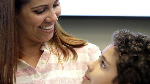 Lidia Karine Souza and her son Diogo De Olivera Filho smile at each other at the Mayer Brown law firm during a news conference shortly after Diogo was reunited with his mother June 28, 2018, in Chicago.