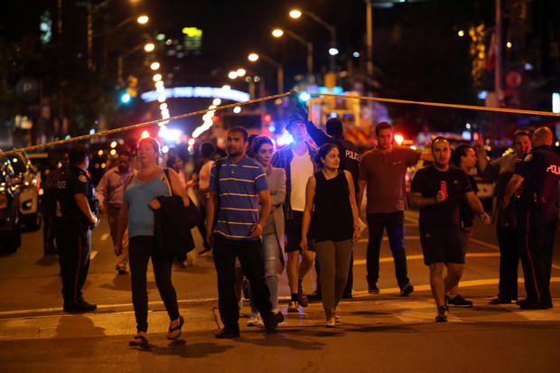 People leave an area taped off by the police near the scene of a mass shooting in Toronto