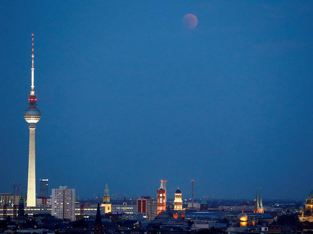 Lunar eclipse is seen above the cityscape and the television tower in Berlin