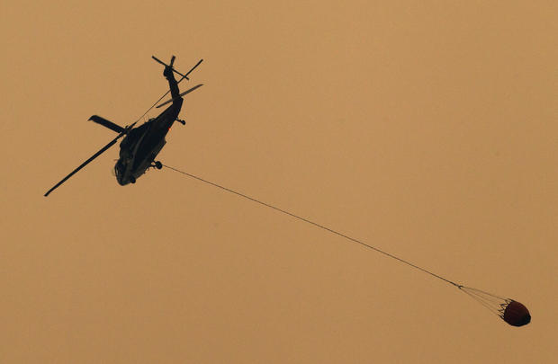 A helicopter prepares to drop water on the Carr Fire as it burns west of Redding