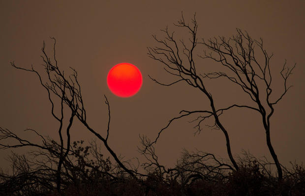 The suns sets over hills burned by the Carr Fire west of Redding
